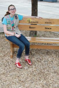 Carolyn Kopp, a sophomore at Muskego High School, Muskego, and graduate of St. Leonard School, Muskego, sits on the buddy bench she arranged to have installed at St. Leonard as part of her Girl Scout Gold Award. (Catholic Herald photo by Ricardo Torres)