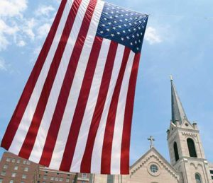 A 48-foot U.S. flag is seen June 24 outside Sacred Heart Church in downtown Peoria, Ill. In his Herald of Hope column, Archbishop Listecki suggests the church is under attack as a faith and a church by civil political forces. (CNS file photo/Tom Dermody, Catholic Post)