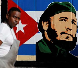An employee of a state-owned candy store looks outside near a painting depicting Cuba's former President Fidel Castro, following the announcement of Castro's death, in Havana, Nov. 27. Castro, who seized power in a 1959 revolution and governed Cuba until 2006, died Nov. 25 at the age of 90. (CNS photo/Reuters)